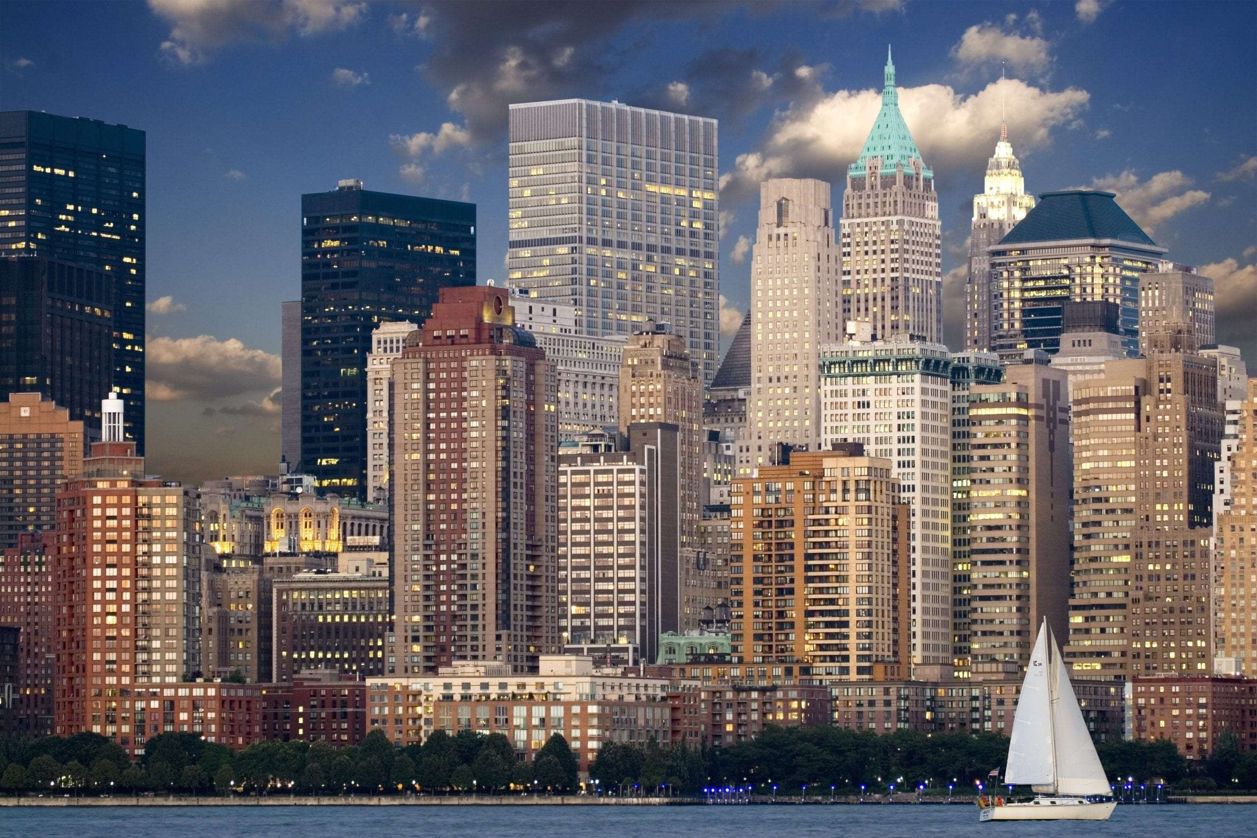 cityscape-during-nighttime-near-body-of-water-and-sail-boat-40142