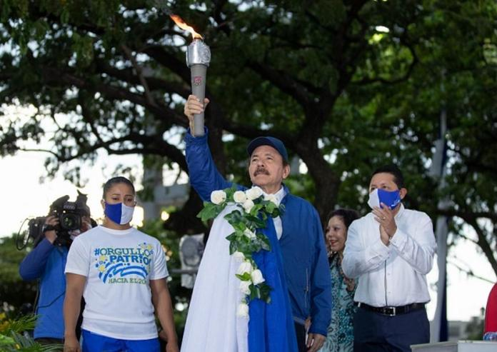 Maskless Ortega receives the Torch of Independence and raises Nicaragua flag