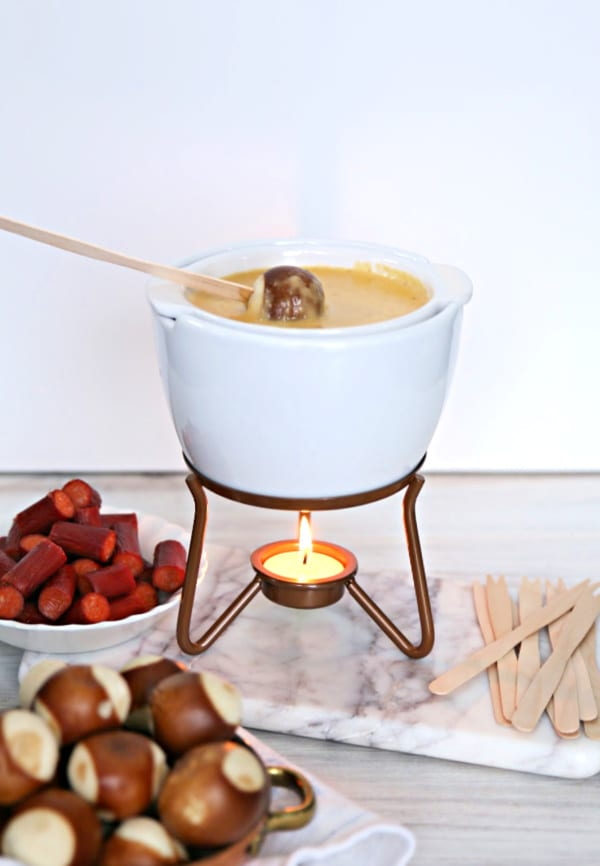 White fondue pot full of cheese fondue