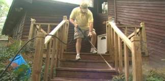 Cleaning deck steps with pressure washer.