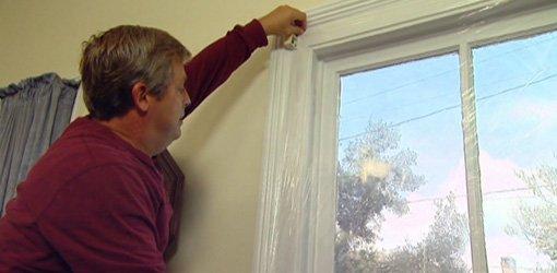 Applying plastic window film to a window.