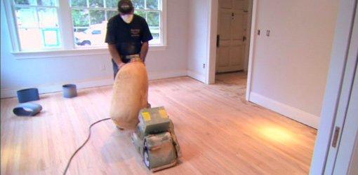 Sanding hardwood floor with drum sander.