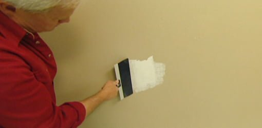 Applying joint compound to patch hole in drywall.
