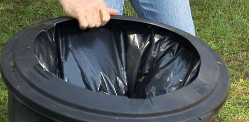 Modified trash can lid with plastic bag inside for bagging leaves.