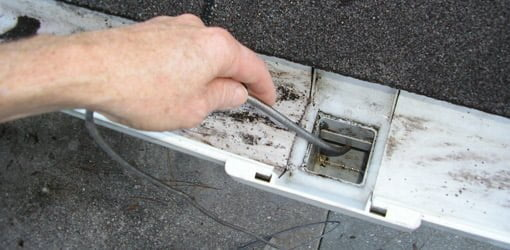 Using a plumber's snake to clear a clog in a downspout