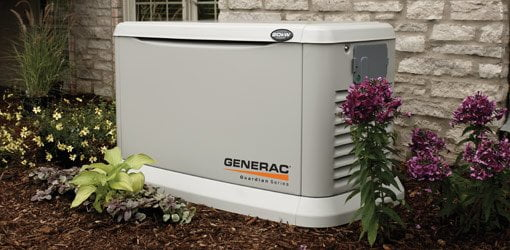 Generac standby generator in yard next to house.