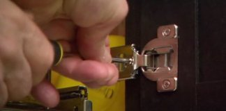 Using a screwdriver to adjust a European style cabinet hinge.