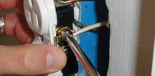 Attaching wires to an electrical wall outlet.