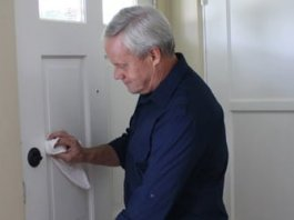 Danny Lipford testing the paint on a door with a rag soaked in denatured alcohol