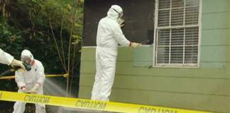 Removing asbestos siding on a house.