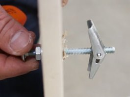 Installing a toggle bolt in a drywall wall.