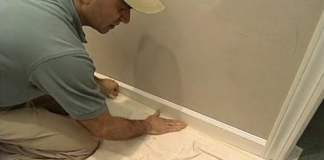 Joe Truini attaching masking tape to drop cloth and trim.