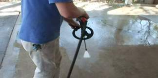 Using a pressure washer to spring clean a concrete patio.