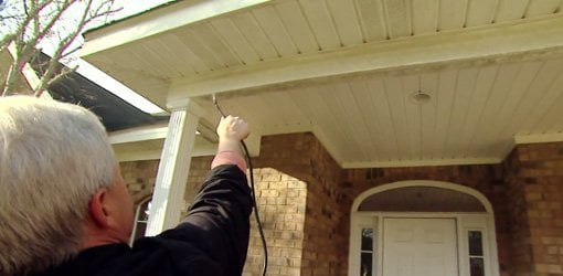 Using a pump up sprayer to remove mold and mildew from eaves on house.