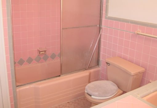 Old pink tile bathroom with tub/shower and toilet.