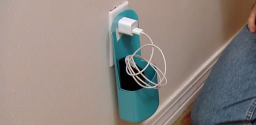 Cell phone charging station made from empty plastic bottle plugged into wall outlet.