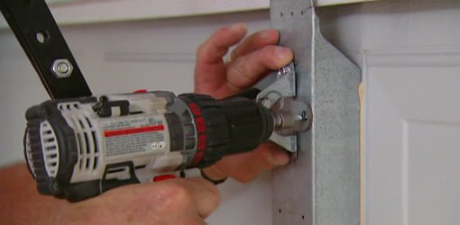 Installing self tapping sheet metal screws in a garage door opener bracket.