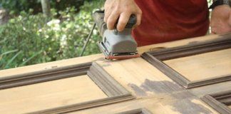 Sanding a badly weathered entry door before refinishing.