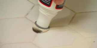 Applying grout stain to the grout lines in a tile floor.