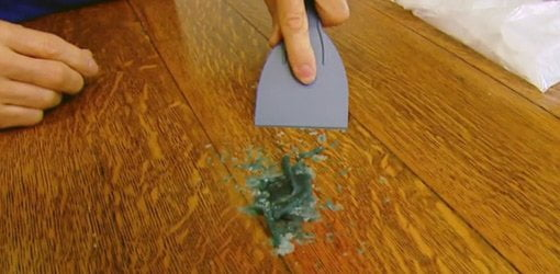Using a plastic putty knife to remove hardened candle wax from a dining room table.