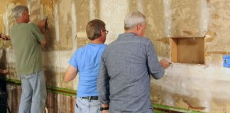Repairing damaged drywall after wallpaper has been removed.
