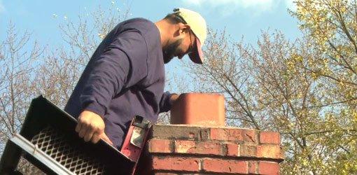 Chimney sweep on ladder inspecting fireplace flue.