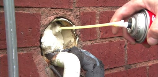 Filling hole with expanding spray foam insulation.