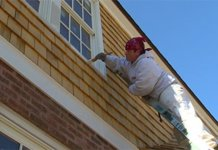 Man on ladder painting house exterior
