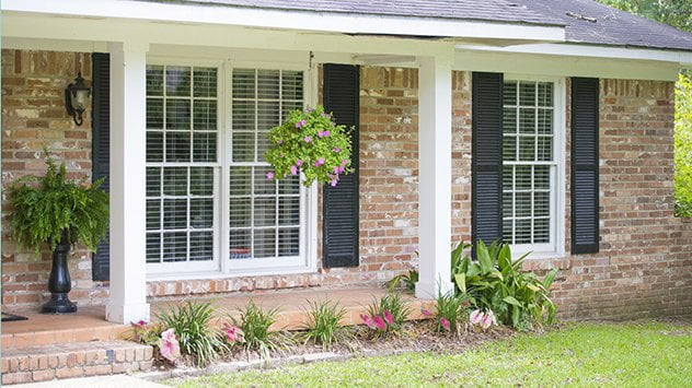 front of house with flower bed and hanging plants