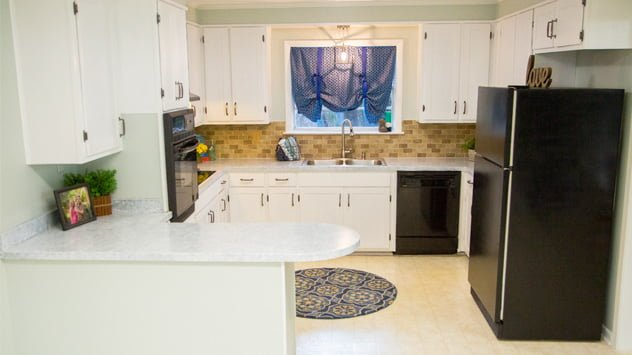 The Rhoads' updated kitchen features white shaker-style cabinets and faux granite countertops.