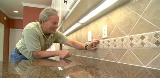 Tile backsplash with mosaic insert.