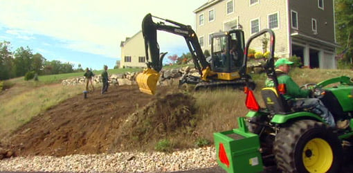 John Deere excavator removing dirt from hillside