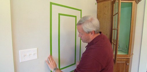 Danny Lipford applying FrogTape painter's tape to wall to create border