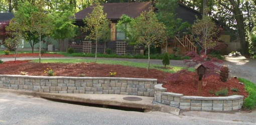 Stackable block retaining wall in front of house.