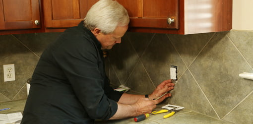 Danny Lipford installing Leviton self-testing  GFCI electrical outlet in kitchen.