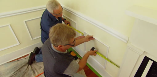 Men measuring and installing faux wainscoting on yellow wall.