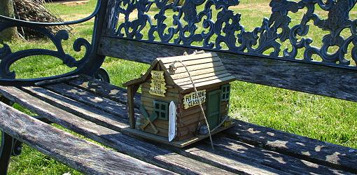 Birdhouse sitting on outdoor bench.
