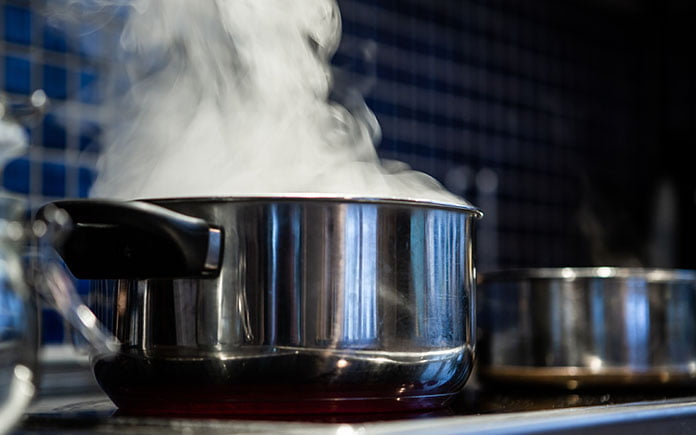 Closeup of steam rising from a stainless steel pot