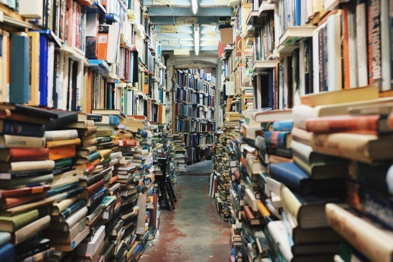 A used bookstore aisle over piled with books.