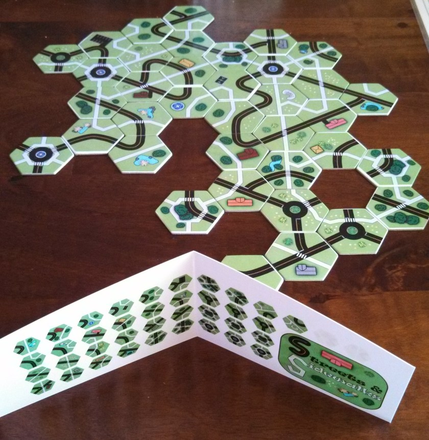 An example board with the final prototype. I started with having 1 tile in your hand at a time, but players didn't have enough options. Eventually I settled on 5 in your hand, but they were unwieldy to hold, so I added a shield so you can keep tiles hidden. Then I put the master tile list on the shield so you can look to see if a piece you need exists and if it has been played yet. That mitigates some of the veteran player advantage.