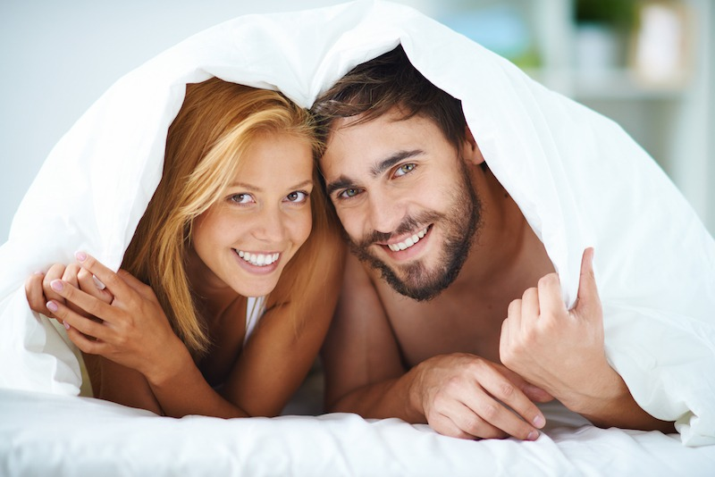 Portrait of happy young couple under blanket looking at camera