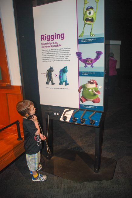 child listening to phone at Science Behind Pixar exhibit