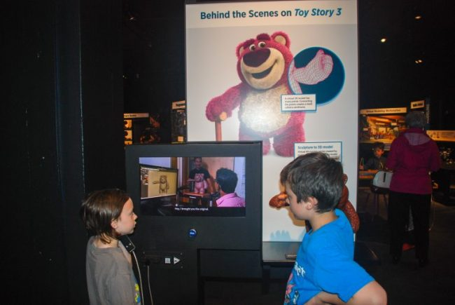 children watching behind the scenes video at Science Behind Pixar exhibit