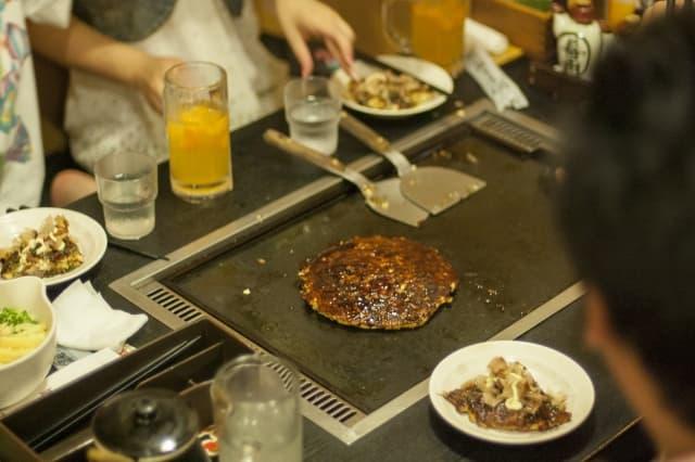 personas comiendo okonomiyaki placa hierro