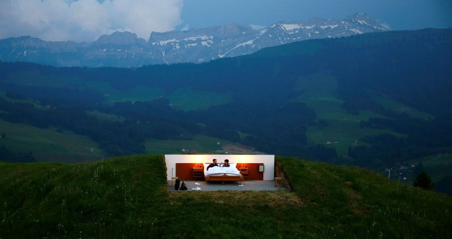 Raphael and Mirjam pose as first guests in the bedroom of the Null-Stern-Hotel land art installation by Swiss artists Frank and Patrik Riklin near Gonten
