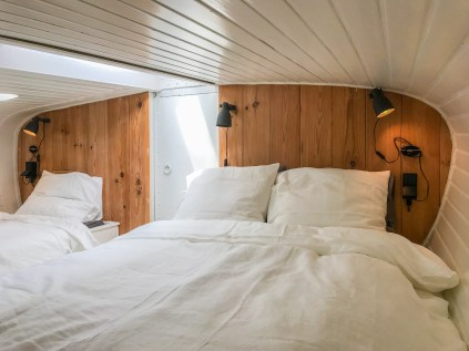 Een twee persoons opgemaakt bed en een een persoons bed .