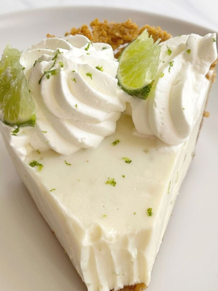 A top shot of key lime pie topped with whipped cream and lime slices.