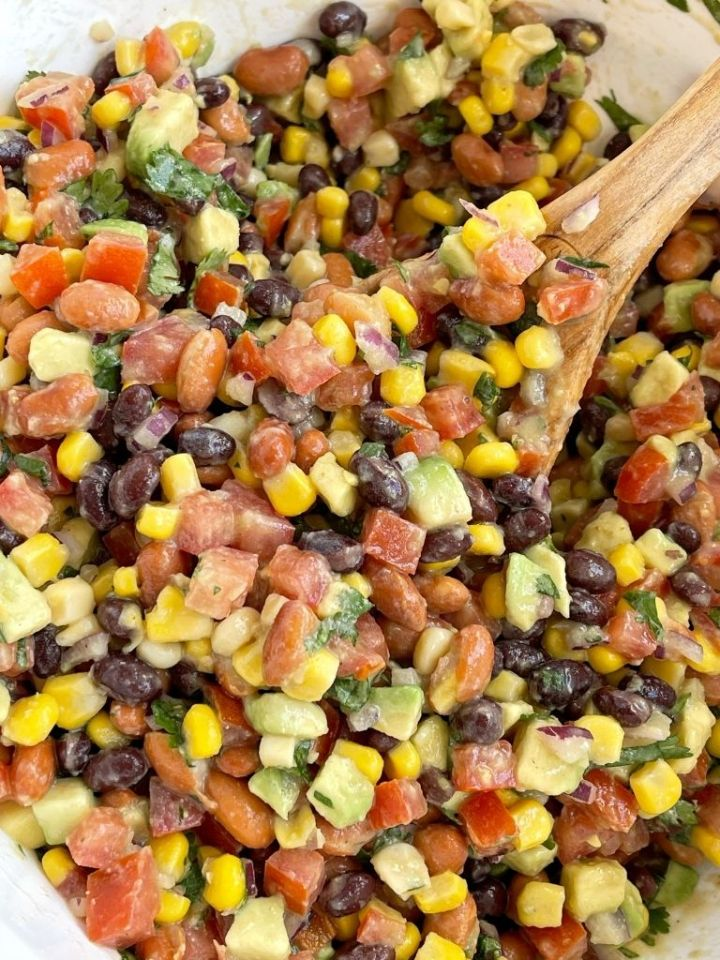 Cowboy salsa recipe inside a bowl with a wooden spoon