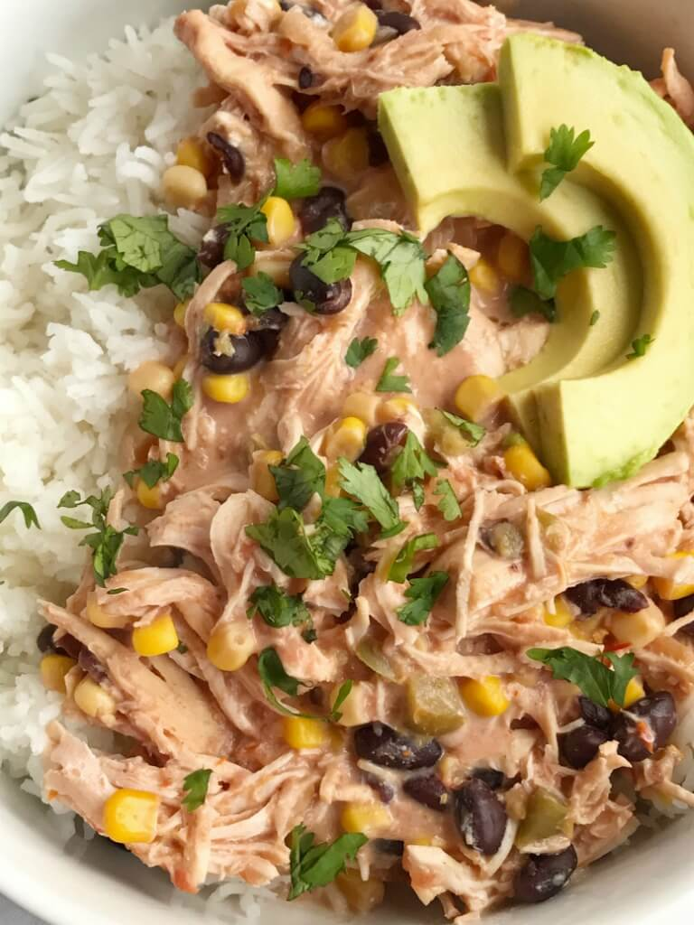 5 ingredients + some spices are all you need for slow cooker creamy fiesta chicken. Takes just minutes to prepare and it's ready when you are. Serve with cooked rice and toppings if your choice. Let everyone create their own creamy fiesta chicken rice bowl for dinner.
