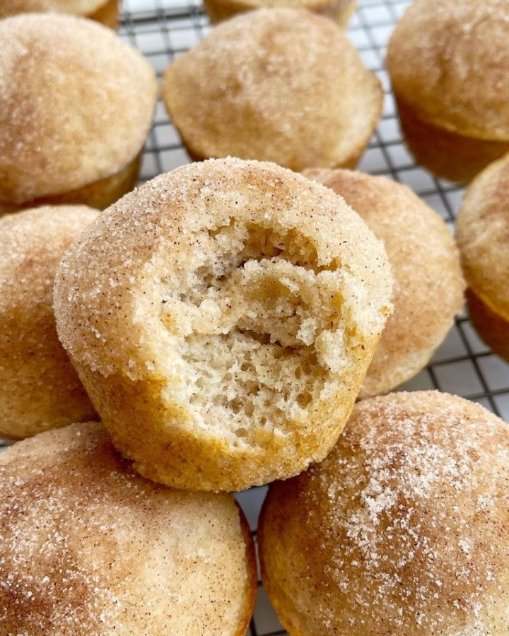 A cinnamon and sugar donut muffins with a bite taken out of it.
